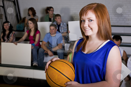 Female Basketball Player stock photo, A female basketball player in the school gym, with her home fans in the background. by Brenda Carson