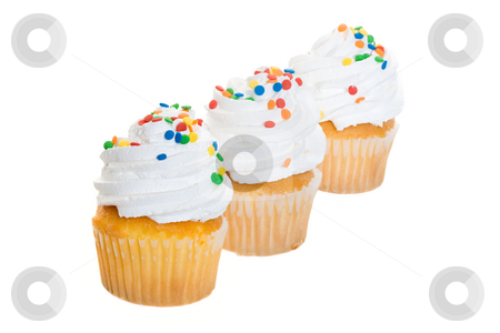 Cupcakes in a Row stock photo, Three cupcakes heaped with icing and candy sprinkles. by Brenda Carson