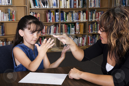 Learning To Count stock photo, A teacher helps a child count on her fingers to figure out a math problem. by Brenda Carson