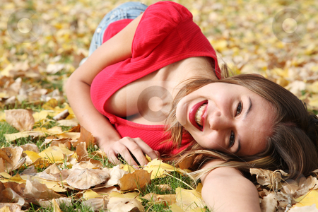 Autumn Sunshine stock photo, A joyful, happy girl laying in the leaves. by Brenda Carson
