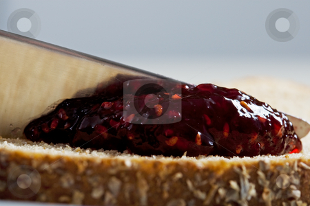 Jam and Bread Macro stock photo, A closeup of a knife full of raspberry jam being spread on multi-grain bread. by Brenda Carson