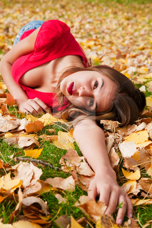 Reaching Out stock photo, A young girl laying in the leaves and reaching out. by Brenda Carson