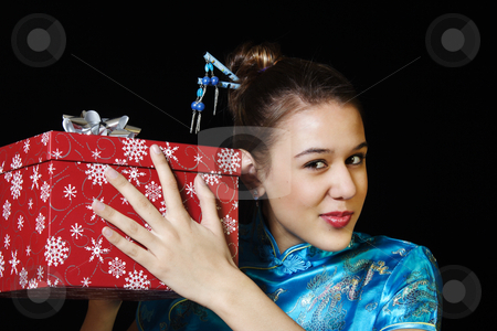 Sounds Like stock photo, An excited girl shaking her Christmas present and trying to guess what's inside. by Brenda Carson
