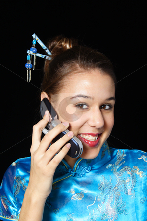 Cellular Customer stock photo, A happy, cell phone user.  Mixed race girl in oriental dress. by Brenda Carson