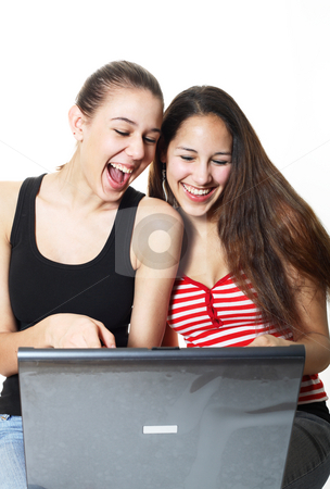 Giggling Teenagers Surf stock photo, Two girls laughing and surfing the internet together. by Brenda Carson