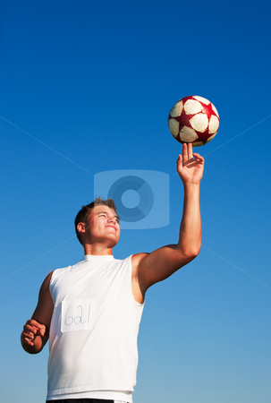 Spinning Soccer Ball stock photo, A young man spinning a soccer ball on his finger in the warm summer sun. by Brenda Carson