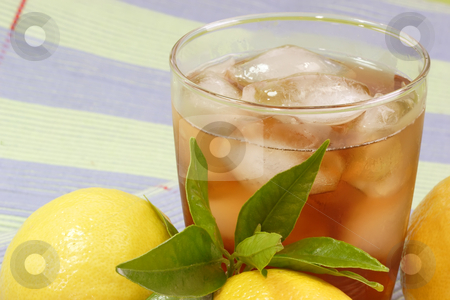 Lemon ice tea_18 stock photo, A glass full of Ice Tea with a lemon slice on green background by Birgit Reitz-Hofmann