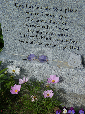 Etched Grave Stone stock photo, Etched Grave Stone with flowers growing around it and sixtie's hippie style sunglasses setting on its ledge. by Dazz Lee Photography