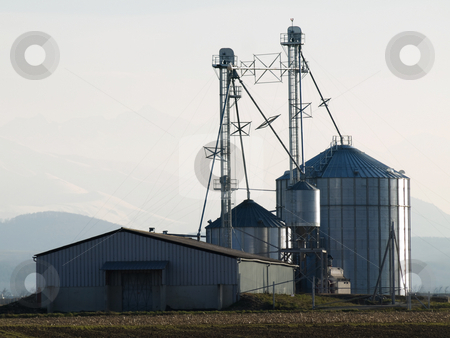 Silos industrial site stock photo, Silos industrial site in the countryside with mountains in the background by Laurent Dambies