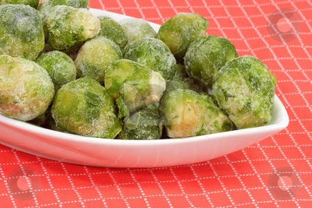 Brussels Sprouts_2 stock photo, Frozen Brussels sprouts in a bowl on red background by Birgit Reitz-Hofmann
