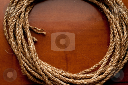 A horizontal image of a coil of rope on a wooden surface with sp stock photo, A horizontal image of a coil of rope on a wooden surface with space for copy in the center of the circle by Vince Clements