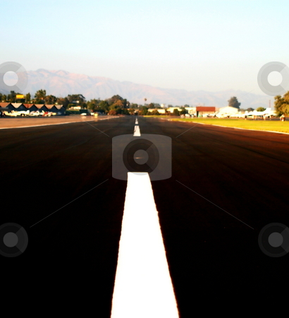 Runway stock photo, White middle line of a runway with some mountains in the background. by Henrik Lehnerer