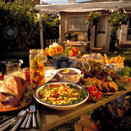 Backyard Feast stock photo, A table full of food sits in the backyard for a summer feast. by Bill Robbins