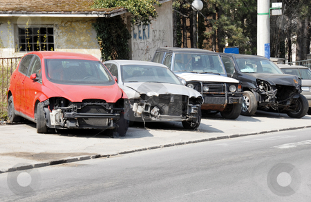 Crashed cars parked stock photo, Four various crashed cars parked on sidewalk by Julija Sapic