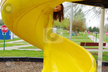 Peek a boo stock photo, Little girl peeking over side of big yellow slide by Sandra Fann
