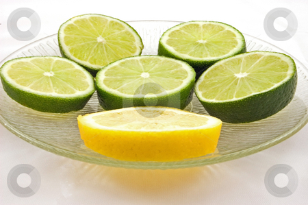 Slices of Fresh Lime and 1 Lemon on Clear Plate stock photo, Slices of fresh green limes and 1 slice of yellow lemon on a clear glass plate, isolated on a white background. by Valerie Garner