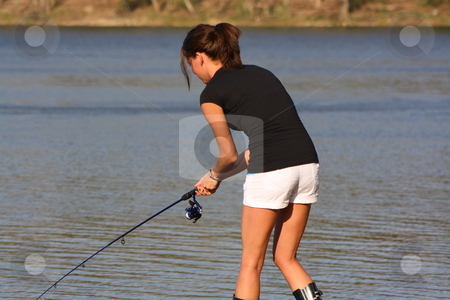 Young woman enjoying a day of fishing stock photo, Rebecca placing tackle on her line for a day of fishing. by Chris Torres