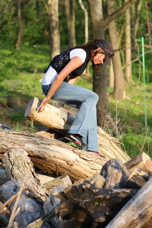 Woman climbing a pile of logs stock photo, Rebecca is excited that she made it to the top of the log pile by Chris Torres