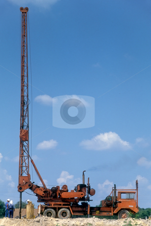 Mobile drilling derrick and crew stock photo, Crew of truck mounted drilling rig sinking foundation holes. by GB Tittle