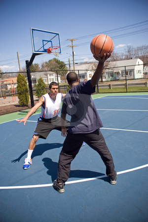 Man Playing Basketball stock photo, A young basketball player is taunting his opponent with the ball while playing one on one. by Todd Arena