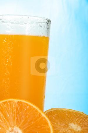 Orange Juice stock photo, Studio shot of glass of orange juice and some oranges over blue ice like background by iodrakon