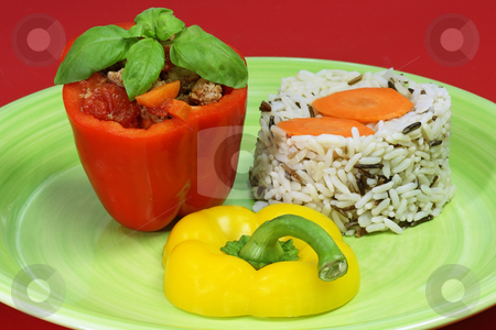 Stuffed paprica stock photo, Stuffed paprica on a plate isolated on red background by Birgit Reitz-Hofmann