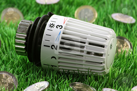 Thermostat stock photo, Radiator thermostat with euro coins on grass meadow by Birgit Reitz-Hofmann