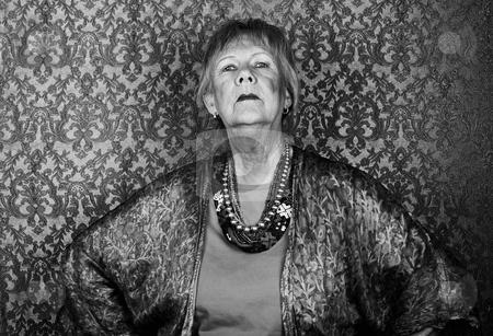 Snooty Senior Woman stock photo, Portrait of snooty senior woman in front of gold background by Scott Griessel