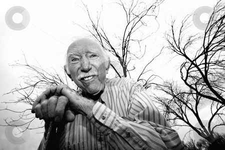 Old man in front of bare trees stock photo, Crazy old man leaning on cane in front of trees by Scott Griessel
