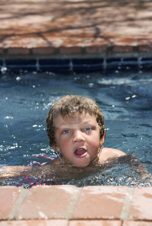 Boy in a Pool stock photo, Cute young boy with blue eyes in a swimming pool by Scott Griessel