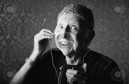 Elderly Hiptser Listening to Handheld Audio Device stock photo, Elderly Hiptser Listening to Small Handheld Audio Device by Scott Griessel