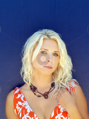 Young blond woman against blue wall melancholy stock photo, Sad blond woman in orange dress with blue background by Jeff Cleveland