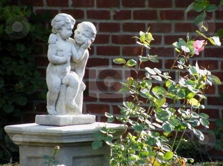 Garden Statue stock photo, Garden Statue beside a flowering rose bush. by Dazz Lee Photography