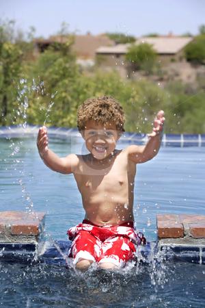 Boy Splashing in a Pool stock photo, Cute young boy splashing in a swimming pool by Scott Griessel