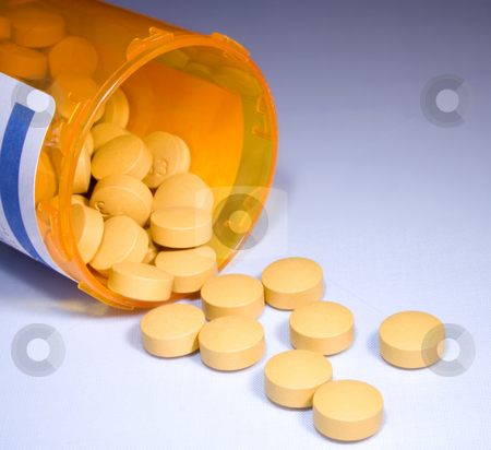 Pills stock photo, Open bottle with pills on surface by Ira J Lyles Jr