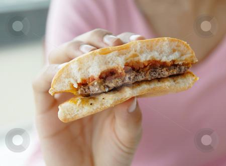 Hamburger in hand stock photo, Half eaten hamburger in teen girl hand closeup by Julija Sapic