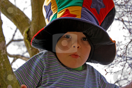 Little Boy in Tree in Mad Hatter Hat stock photo, This wacky photo is a little boy climbing a tree in a wacky colorful mad hatter type hat. by Valerie Garner