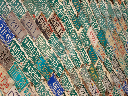 Wall full of License Plates stock photo, A wall is covered with colorful license plates. by Ben O'Neal