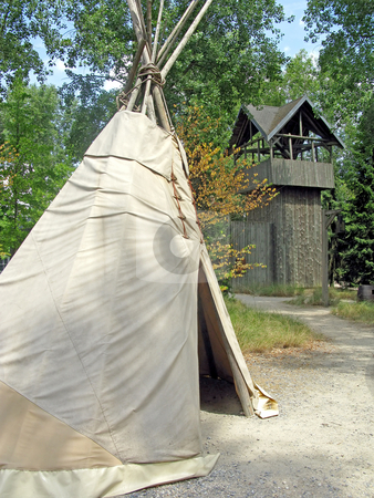 Teepee stock photo, Teepee in a forest with a wooden fort behind. by Lucy Clark