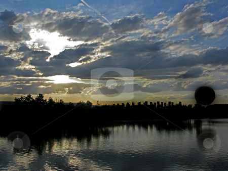 Balloon Silhouette Sunset stock photo, A silhouette of a balloon and surroundings at sunset across a lake. by Lucy Clark