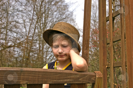 Child on Garden Swing Sad stock photo, This child sitting on a garden swing is wearing a hat and looking at small flowers.  Her facial expression is one of sadness and being upset. by Valerie Garner