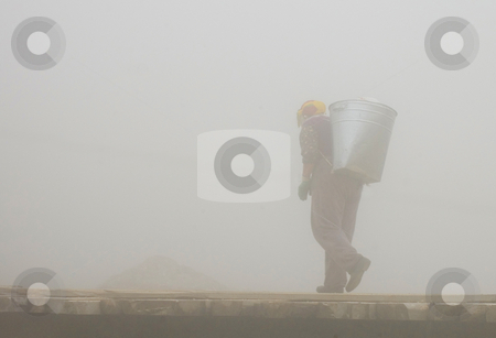 The carrier stock photo, Woman carrier with heavy carriage walking in the fog by Kobby Dagan