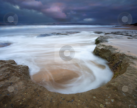 Stormy Sunrise stock photo, A small blowlike depression in the limestone becomes a swirling pot for the risng tides on Knights Beach as stormy clouds reflect some color and light from sunrise. by Mike Dawson