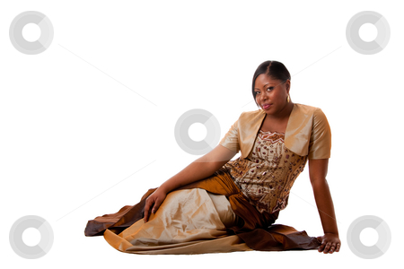 Beautiful African woman stock photo, Beautiful African American woman in brown with gold dress, sitting laying on floor, isolated by Paul Hakimata