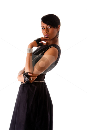 African fashion model stock photo, Beautiful modern classy African American female fashion model in black dress with silver chains and biker gloves looking sideways thinking, isolated by Paul Hakimata