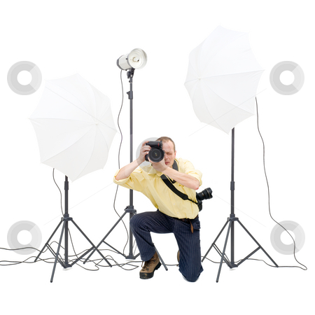 Studio photographer stock photo, A professional photographer in a studio, surrounded by three strobes by Corepics VOF