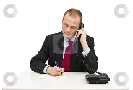 Customer support stock photo, A businessman behind a desk taking notes whilst intentively listening to a client on the phone by Corepics VOF