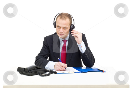 Business call stock photo, A businessman in a gray suit and tie behind a desk making a telephone call using a head set by Corepics VOF