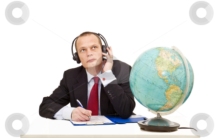 Understanding foreign languages stock photo, A businessman with a head set on listening attentively to a conversation in another language, represented by the globe on his desk by Corepics VOF