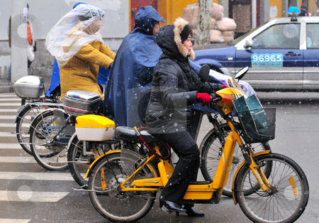 Chinese motorcyclists  stock photo, Chinese motorcyclist in shanghai street in a snowy day by Kobby Dagan